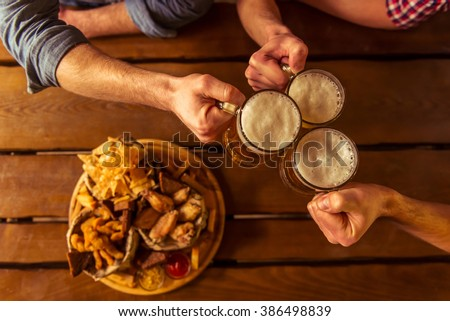 Top view of hands clanging glasses of beer together, near big wooden tray with delicious snacks, on wooden background