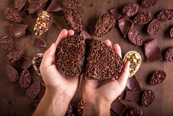 Top view of hands holding a cracked stuffed chocolate easter egg with grated chocolate on the top on the foreground. Lots of mini easter eggs and cracked chocolates on a wooden table at the background