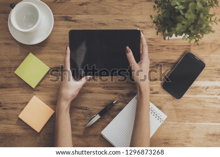 Top view of hands holding tablet table background. Creative space. Female hands hold computer tablet on wooden desktop. Interactions with digital devices. Digital technologies concept. #1296873268