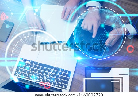 Top view of hands of business people with digital tablet and laptop on an office table. Futuristic glowing icons. HUD infograph. Toned image double exposure Elements of this image furnished by NASA #1160002720