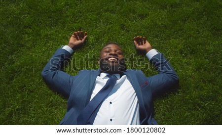 Top view of handsome afro businessman dressed in stylish formal suit resting on green grass. Happy african-american entrepreneur relaxing on lawn and smiling enjoying break outdoors Photo stock ©