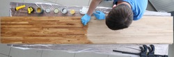 Top view of handy man covering wooden desk with special oil
