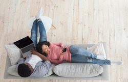 Top View Of Happy Black Couple Spending Time At Home. Man Using Laptop And Woman Surfing Internet On Smartphone, Copy Space