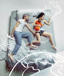 Top view of happy funny family with one newborn child in bedroom. Enjoying being together. Happy family in bed and their dreams about travel, shopping, trip, vacation, holidays, tourism. Painted dream