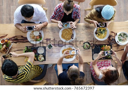 Top view of happy people taking photo of food on mobile phone before gathering for eating food, enjoying the party and communicate with family and friends at table on holiday, soft focus background