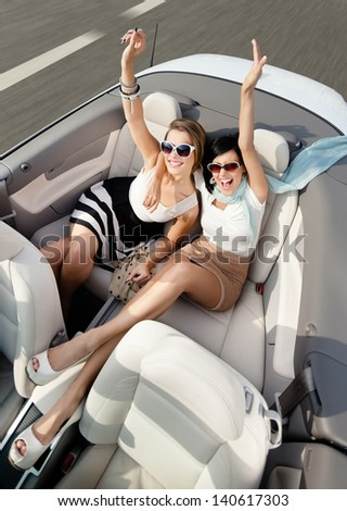 Top view of happy women in sunglasses with their hands up sit in the car