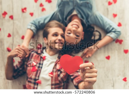 Top view of happy young couple looking at camera and smiling while lying on wooden floor. Guy is holding a red paper heart