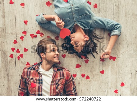 Photo of Top view of happy young couple looking at each other and smiling while lying on wooden floor. Girl is holding a red paper heart