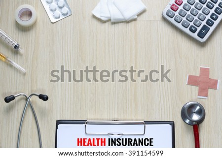 Top view of Health Insurance policy with stethoscope, hypodermic syringe, plaster, gauze, medicine, tape and calculator