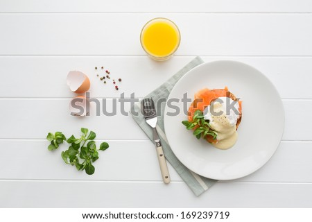 Top view of healthy breakfast with poached eggs royale (benedict), fresh orange juice and green salad #169239719