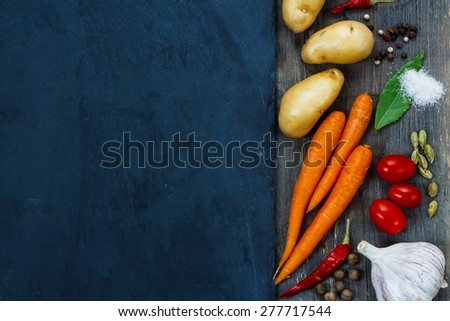 Top view of Healthy eating background with fresh organic vegetables, spices and herbs over slate. Healthy food from garden.