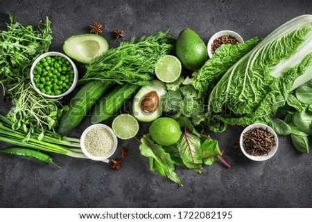 Top view of healthy organic food: green vegetables, seeds and herbs on dark background. Source of protein for vegetarians.