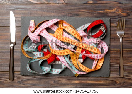 Top view of heap of colorful measuring tapes in plate on wooden background. Diet concept with copy space. Stock photo ©