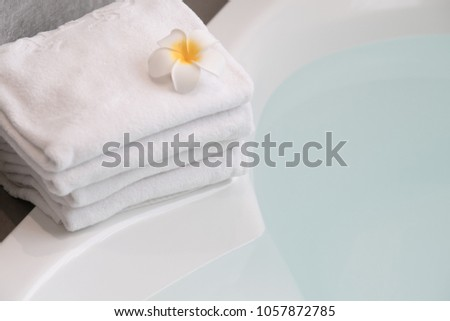 Top view of herbal ball bathtub with towel and frangipani flower