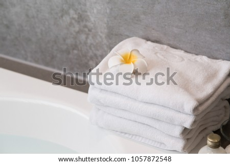Top view of herbal ball bathtub with towel and frangipani flower,massage oil