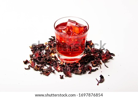 "Photo of  top view of hibiscus infusion iced tea called ""Rosa de Jamaica"" o ""aguas frescas"" in Mexico and Central America, served on a glass isolated on white background."