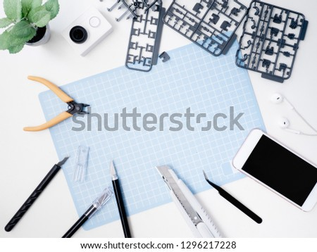 top view of hobbies concept with cutting mat, Plastic model part kits and tool kits on white background with copy space. #1296217228