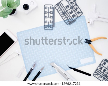 top view of hobbies concept with cutting mat, Plastic model part kits and tool kits on white background with copy space. #1296217231