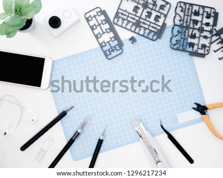 top view of hobbies concept with cutting mat, Plastic model part kits and tool kits on white background with copy space. #1296217234