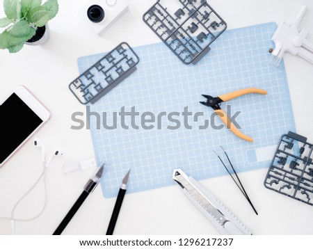 top view of hobbies concept with cutting mat, Plastic model part kits and tool kits on white background with copy space. #1296217237