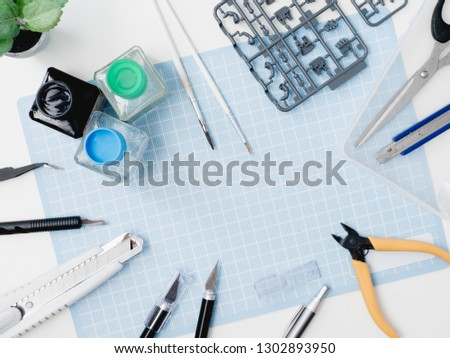 top view of hobbies concept with cutting mat, Plastic model part kits and tool kits on white background with copy space. #1302893950
