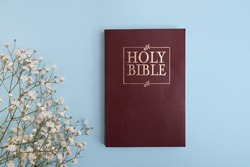 Top view of holy bible on round with flowers on blue background