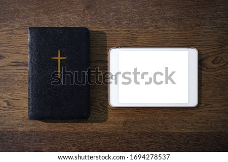 Top view of holy bible with blank tablet on wooden table, Church online Sunday  services new normal concept, Home church during quarantine coronavirus Covid-19, Study bible worship online concept