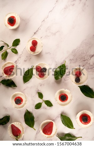 Top view of homemade cheesecakes with homemade strawberry sauce and accompanied by strawberries, blackberries, raspberries and green leaves on white background.