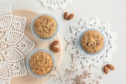 Top view of homemade fresh baked banana cupcakes muffins in blue liners arranged on a table and natural wood plater with white crochet doilies and almonds
