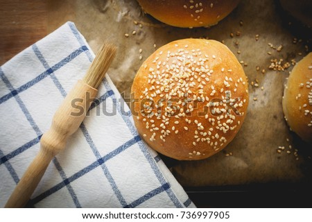 Top view of homemade sesame buns on a wooden chopping board with a striped white kitchen cloth and a pastry brush. Landscape format.