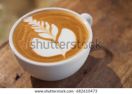 Top view of hot coffee cappuccino latte art in white ceramic cup on wooden plate #682610473