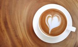 Top view of hot coffee latte art heart shape foam on wood table background
