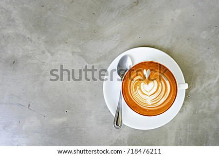 Top view of hot coffee latte with latte art,A cup of coffee , cappuccino art ,Cappuccino with beautiful foam and spoon in white cup ,Copy space.