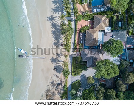 Top view of houses on the palm beach, pool and boat near a wooden pier. Aerial Top view landscape.