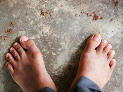 Top view of human bare foot and wear grey trousers on the grey cement floor.