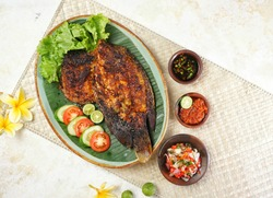 Top view of Ikan Bakar Jimbaran. A Balinese dish in the form of charcoal grilled fish, served with Plecing Kangkung and three kinds of chili sauce, Sambal Matah, Sambal Kecap and Sambal Terasi.