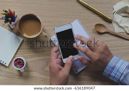 Top view of in man's hands smartphone on a wood floor in home. Vintage tone filter smooth is concept. Human using is chatting social networks. Pastel tone colors. #636189047