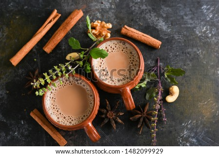 Top view of Indian Masala Chai or traditional beverage with tea, milk and spices Kerala India. Two cups of organic ayurvedic or herbal drink India, good in winter for immunity boosting.