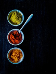 Top view of indian spices on metal pots on black background with empty space on the right for text or label