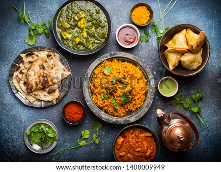 Top view of Indian traditional dishes and appetizers: chicken curry, pilaf, naan bread, samosas, paneer, chutney on rustic background. Table with choice of food of Indian cuisine, dinner/buffet