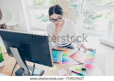 Top view of intelligent stylish young asian graphic designer is working with colors samples, pensive. She is a successful self employed artist #714019627