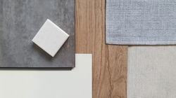 top view of interior finishing material combination containing wooden and concrete vinyl tiles ,white laminate , grey fabric ,grey interior wallpaper and synthesis stone samples.