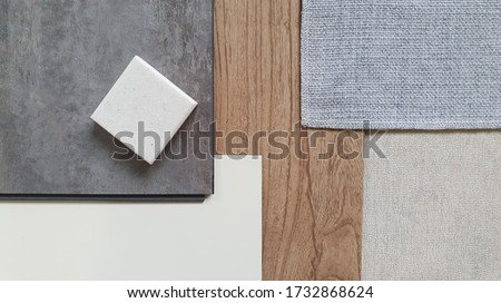Photo of  top view of interior finishing material combination containing wooden and concrete vinyl tiles ,white laminate , grey fabric ,grey interior wallpaper and synthesis stone samples.