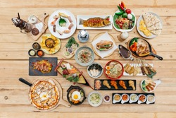 Top view of International Foods on wooden table include Sushi, Sashimi, Nachos, Spaghetti, Naan, Sandwich, Noodle, Steak, Ramen. Yakitori, Pizza, Bibimbap, Fried Chicken Wings, Brownie Frappe.