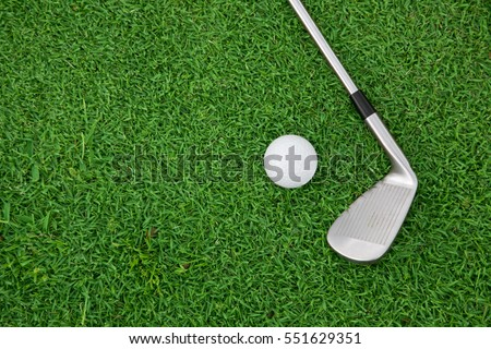 top view of iron golf club and ball on a green grass #551629351