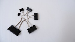 Top view of isolated black binder clips (or fold back clips office, paper clip) in different sizes with white background.