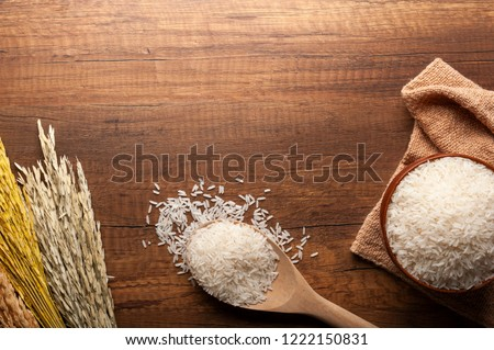 Top view of jasmine rice in a bowl on dark wooden table with rice plants, ear of rices with jasmine rice in a bowl , rice scatter on the floor.
