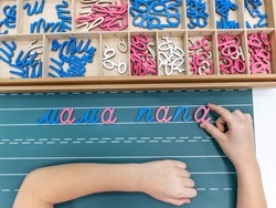 Top view of kids hands building words by using colored Montessori movable alphabet from the wooden tray on blackboard. Concept of learning,practicing hand-eye coordination and developing motor skills.