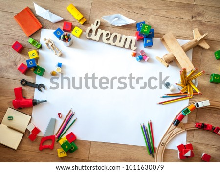 Top view of kids toys on floor on white paper. Educational toys blocks, train, railroad, plane. Toys for preschool and kindergarten or daycare. Kids toys frame on wood background. Copy space for text
