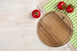 Top view of kitchen cutting board over wooden background